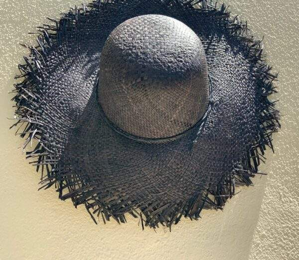 Black straw hat with frayed edge